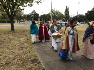 People in REgency dress with cloaks and shawls promenading to the picnic