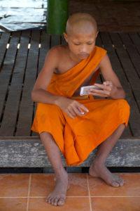 Jeune moine avec la cigarette et le mobile phone