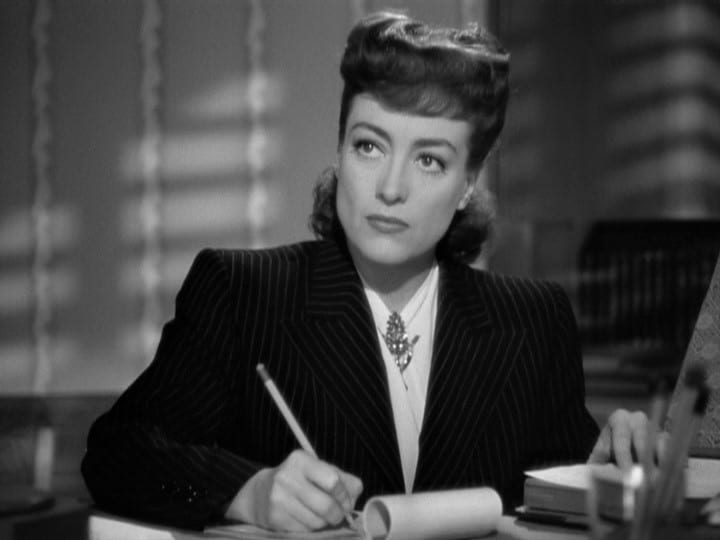 Movie still of Joan Crawford in business suit seated at desk holding a pencil from Mildred Pierce