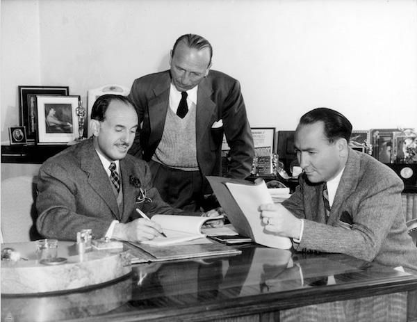 photo of jack l. warner, michael curtiz, hal wallis poring over screenplay and paperwork in office