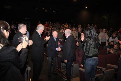 photo of Norman Lloyd shaking hands with gentlemen in suits as audience applauds for him