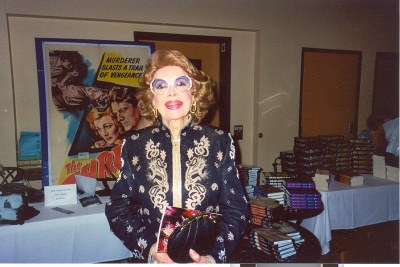 photo of Jayne Meadows standing amidst tables piled with copies of books