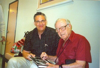 photo of Stanley Rubin and Alan K. Rode seated together as Stanley autographs black and white photo
