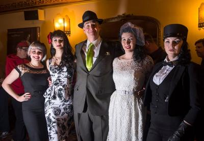photo of Alan K. Rode in suit and fedora posing with four women all dressed up in period 1940's attire