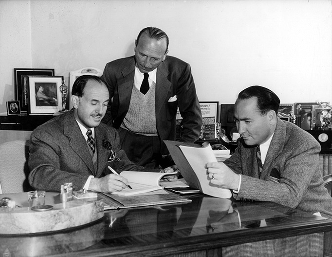 photo of Jack Warner, Michael Curtiz, Hal Wallis gathered at executive desk with movie scripts and contracts