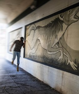 """Up in the air as he runs """"chasing"""" the skinwalker image in the mural. Motion blur used on the arm & leg in back. there is a large painting so that art is most of the image."""