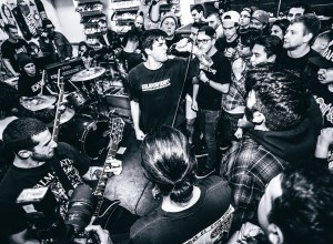 Black and white photo of Forced Order playing in front of a packed room. The photo was taken by Kiabad Meza.