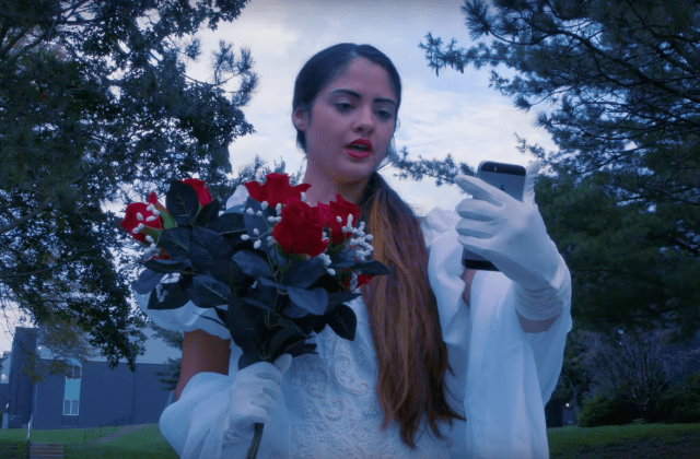 "A scene from Citizen's video for their new single ""In the Middle of It All"" that shows a woman dressed in a wedding dress speaking to her phone."
