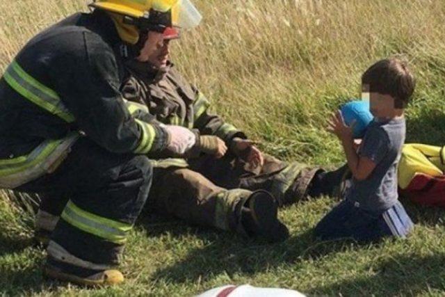 Conmovedora imagen de dos bomberos que distraen a un nene tras un accidente