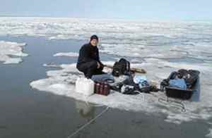 Researcher James McClelland sampling water during ice break-up in Kaktovik Lagoon, Alaska.  Credit: Kenneth Dunton