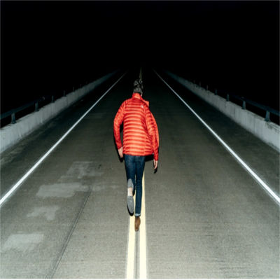 A person running down the middle of a dark road