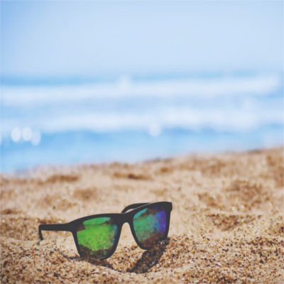A pair of sunglasses on the beach