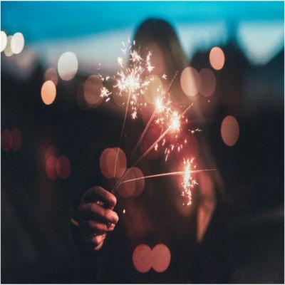 A person holding a lit sparkler