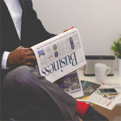 A man in a suit reading the business section of the newspaper