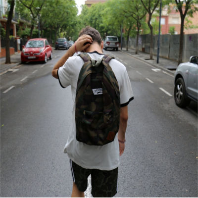 A person walking down the street wearing a backpack