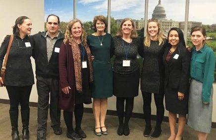 Group photo of 8 people in front of artwork of the US Capitol