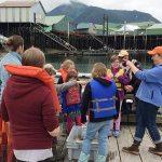 children and chaperones standing on dock