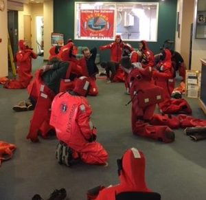 people practicing putting on marine survival suits