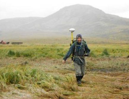 man walking on tundra carrying scientific equipment