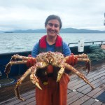 Young woman on a boat deck holding large crab