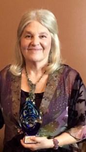 Woman smiling, holding award