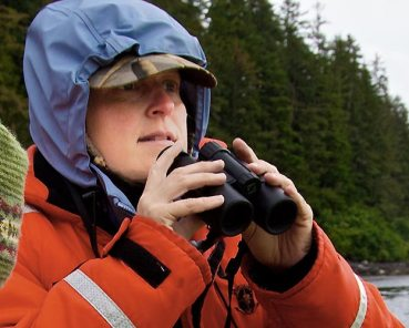 Sunny Rice in orange jacket and blue hood holding binoculars