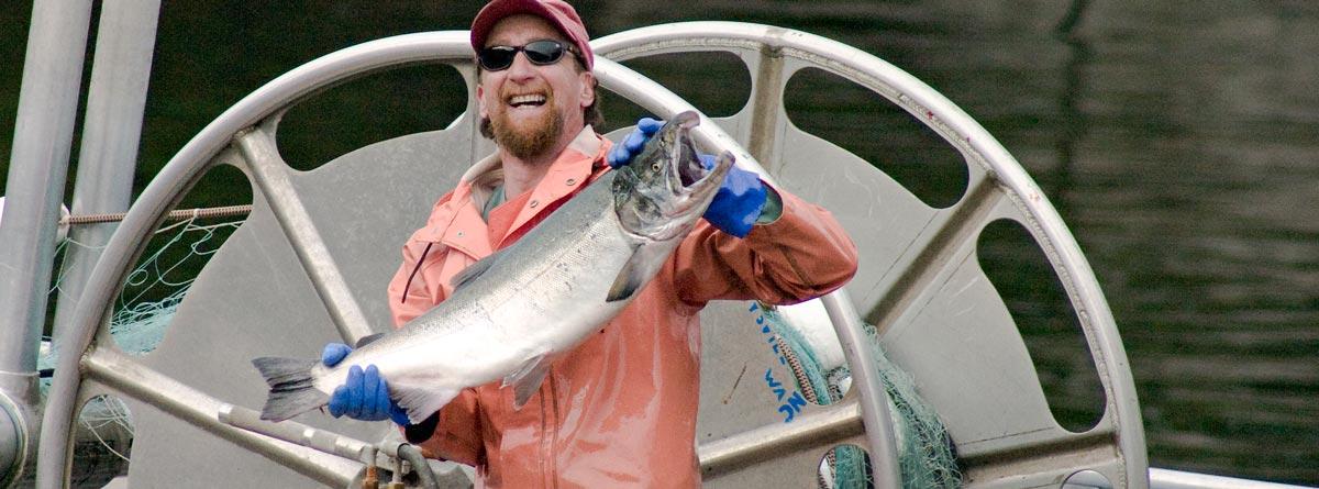 Fisherman on boat holding up big salmon
