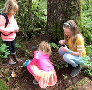 Three girls examine the base of a big tree