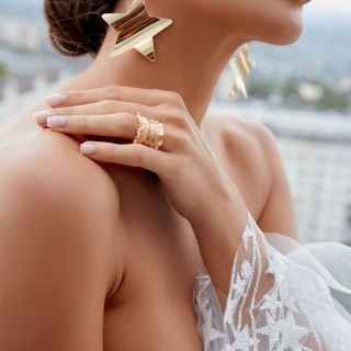 crop fashionable bride in wedding dress and gold accessories