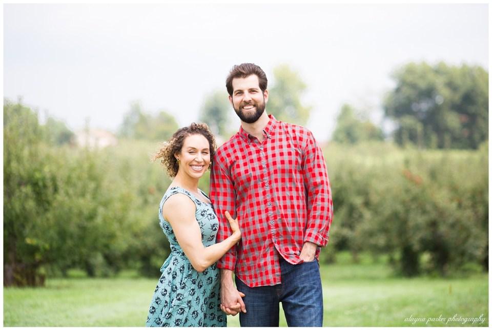 man and woman looking at camera at apple orchard