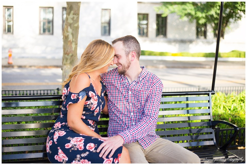 A picture of a newly engaged couple sitting on a bench outdoors, romantically snuggling together