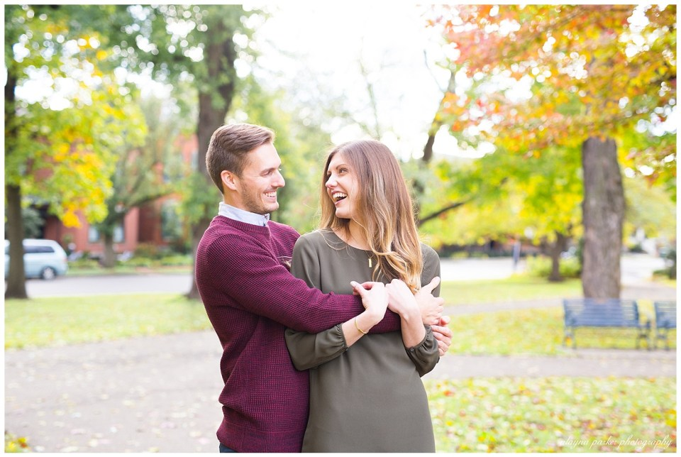 A photograph of a newly engaged couple embracing and laughing together outdoors in a park with the trees showing their fall colors in German Village by Alayna Parker Photography  - Columbus  engagement photography