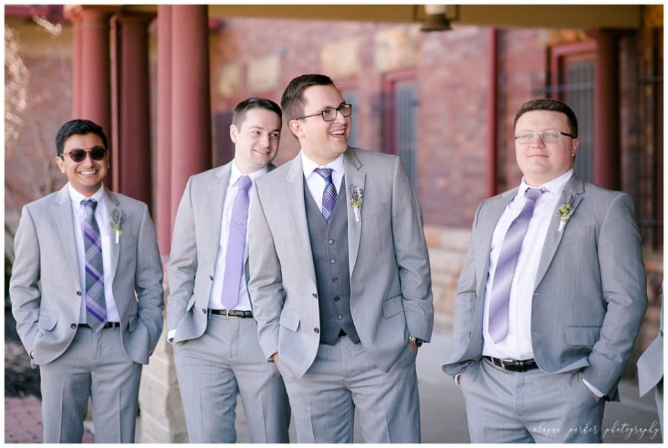A photograph of the groom and some of his groomsmen smiling and pausing together in their wedding tuxedos at Station 67  by Alayna Parker Photography  - Columbus OH wedding photography