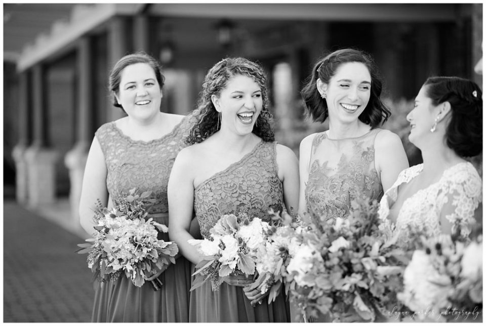 An image in black and white of the bride and bridesmaids laughing and relaxing together at Sation 67 in downtown Columbus by Alayna Parker Photography  - Columbus OH wedding photographer