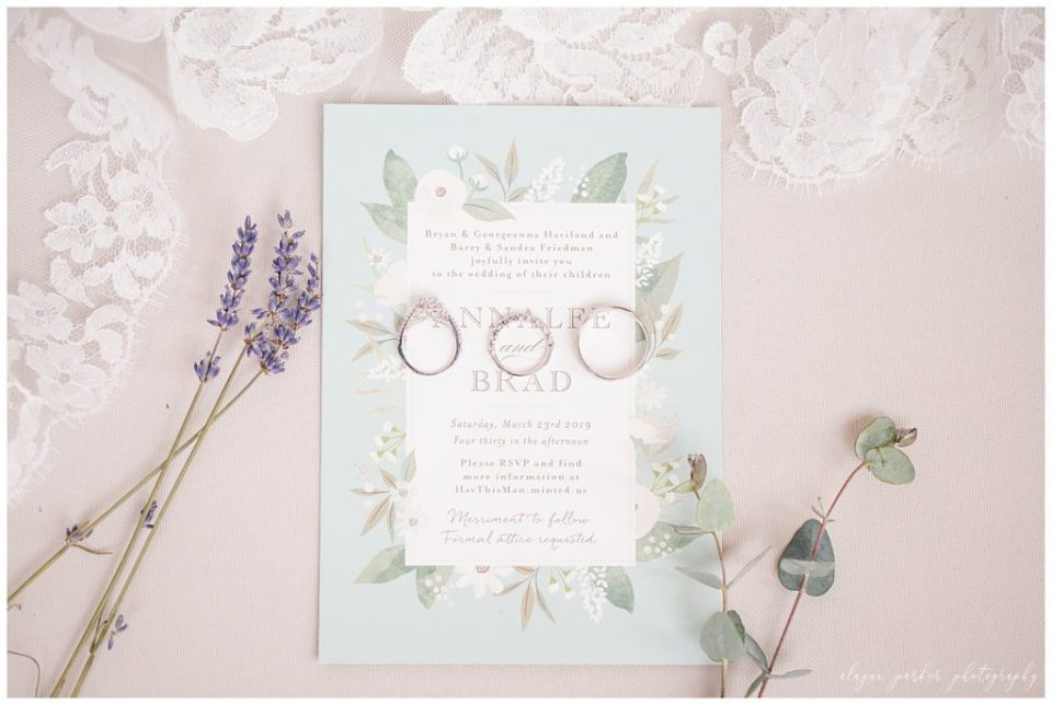A photograph of a closeup of the wedding rings resting on the wedding invitation, surrounded by flowers and greens at Station 67 , near the Scioto River by Alayna Parker  - Columbus OH wedding photography
