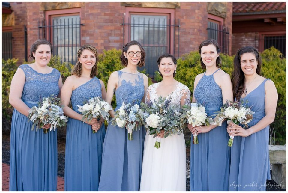 A picture of a bride and her bridesmaids all in blue, smiling as they line up together outdoors at Sation 67 in downtown Columbus by Alayna Parker  - Columbus  wedding photographers