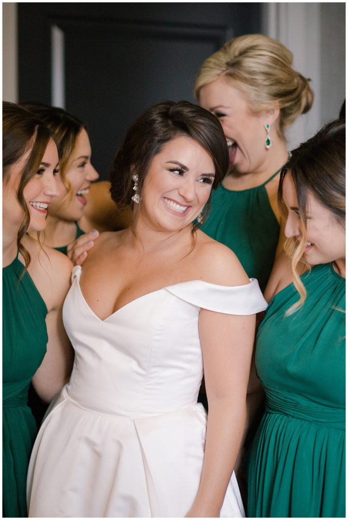 A photograph of a happy bride smiling and relaxing with her bridesmaids just before the wedding at the Hotel LeVeque by Alayna Parker Photography  - Columbus OH wedding pictures