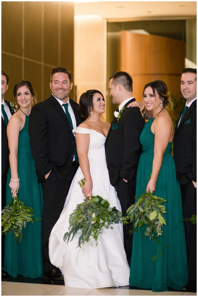 An image of the bride and groom standing with some of their wedding party as they line up together after the ceremony at a Hotel LeVeque wedding by Alayna Parker Photography  - Columbus Ohio wedding photographers