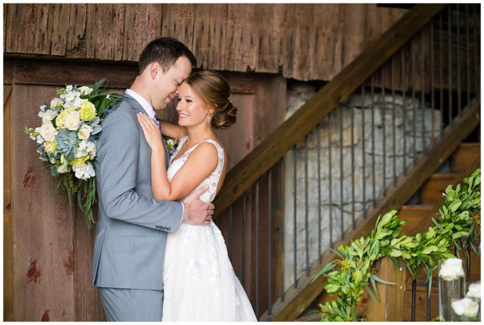 An image of the bride and groom holding each other tight, smiling in a rustic barn setting at the Buckeye Barn wedding venue by Alayna Parker Photography  - Columbus Ohio wedding pictures