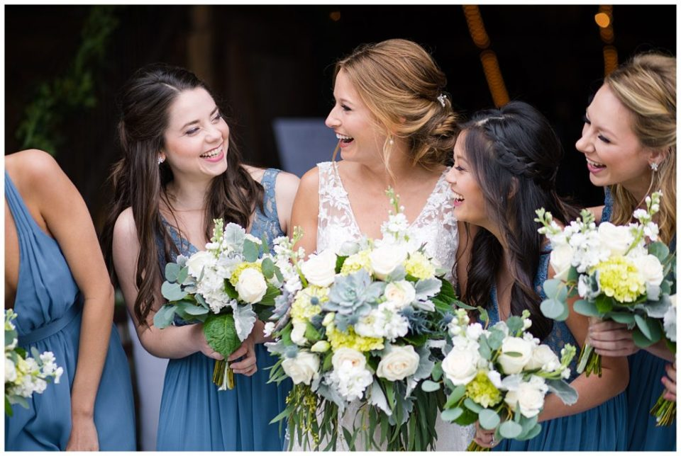 A photograph of the bride and her bridesmaids relaxed and laughing together after the wedding at the Buckeye Barn wedding venue by Alayna Parker Photography  - Columbus OH wedding photographer