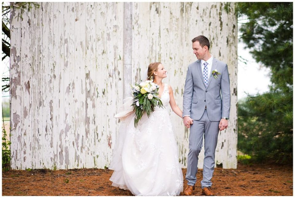 A picture of a bride and groom holding hands and smiling at each other as they stand by rustic wall outdoors at the Buckeye Barn wedding venue by Alayna Parker Photography  - Columbus  wedding pictures