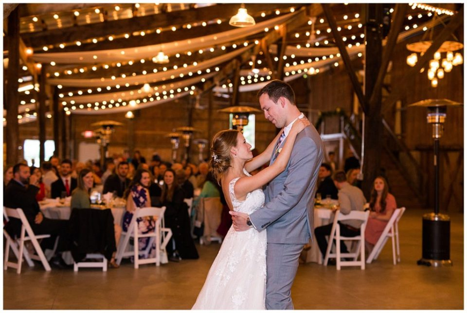 An image of a bride and groom romantically dancing their first dance at the wedding reception at the Buckeye Barn in Piqua Ohio by Alayna Parker  - Columbus Ohio wedding images