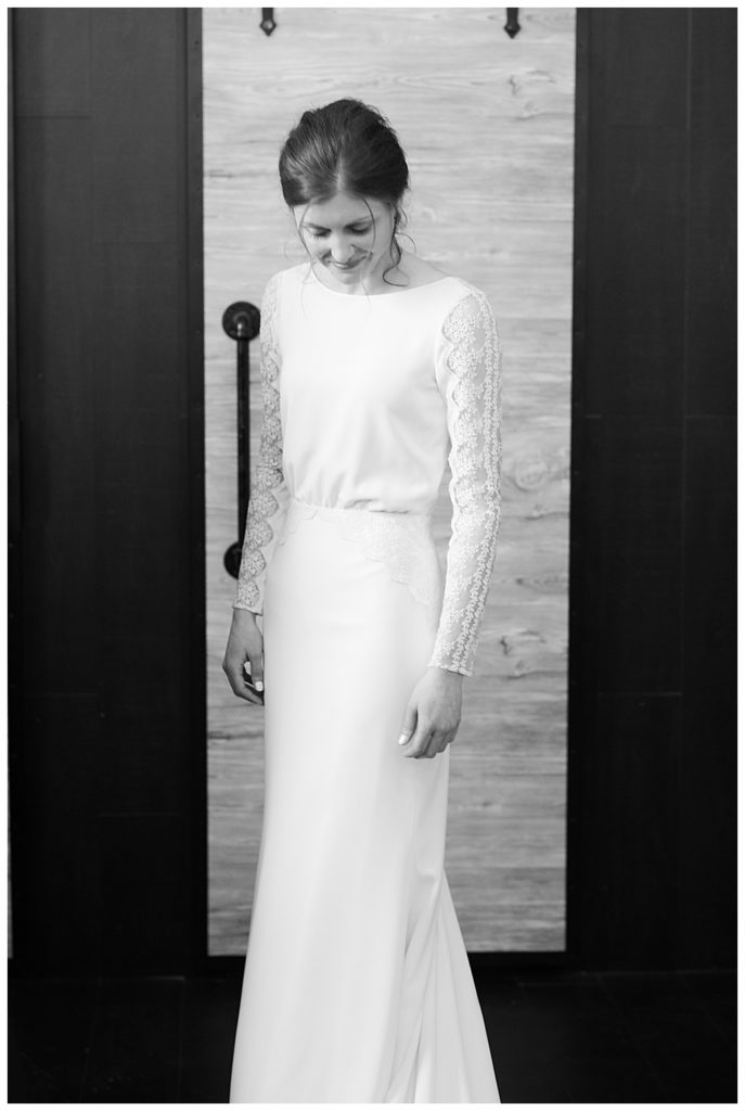 black and white image of bride smiling as she looks down after getting dressed