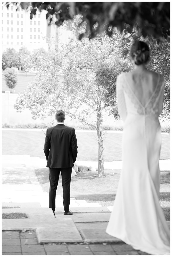 black and white image of groom waiting to see his bride