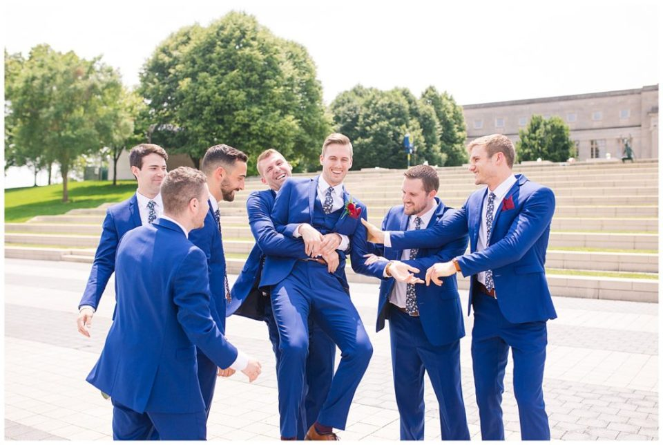 groomsmen picking up and hugging groom