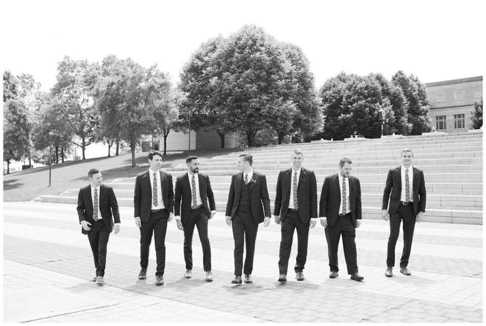 black and white image of groom and groomsmen walking at genoa park