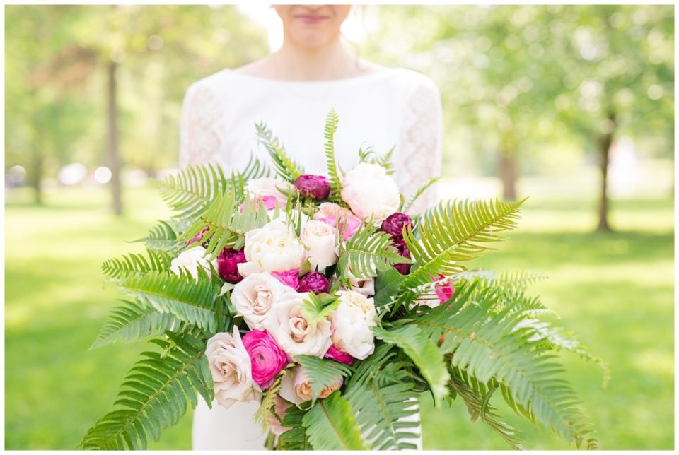bride holding bouquet of pale pink roses, hot pink ranunculus, peach roses, and ferns
