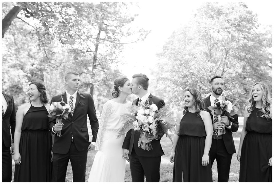 black and white image of bridal party walking and bride and groom kissing