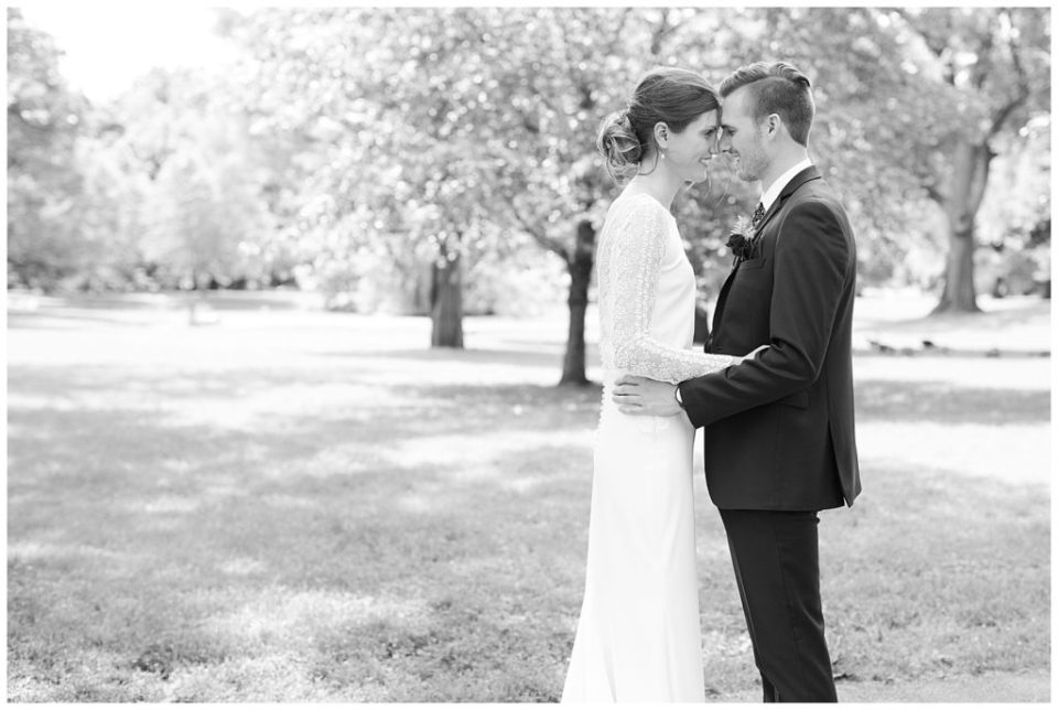 An image in black and white of a bride and groom holding each other, tenderly touching foreheads, as they stand outdoors at Dock 580, in the historic Smith Bros Hardware building by Alayna Parker  - Columbus Ohio wedding photos