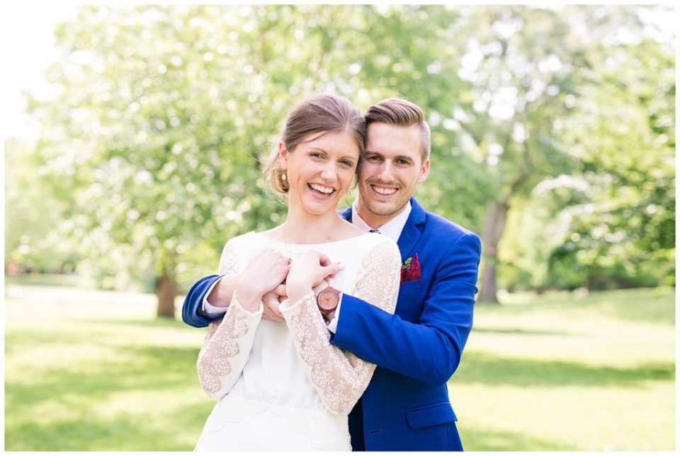 A photograph of a smiling groom holding his bride from behind as she grasps his hands at Dock 580, in the hostoric Smith Bros Hardware building by Alayna Parker  - Columbus OH marriage photographer